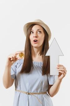 Młoda elegancka kobieta w niebieskiej sukience, kapeluszu trzymając bitcoin, moneta w złotym kolorze, strzałka w górę wartości na białym tle. finanse i biznes, koncepcja wirtualnej waluty. powierzchnia reklamowa. skopiuj miejsce.