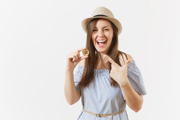 Młoda elegancka kobieta w niebieskiej sukience, kapeluszu z długimi włosami, trzymając monety bitcoin złotego koloru na białym tle. finanse, biznes koncepcja wirtualnej waluty online. powierzchnia reklamowa. skopiuj miejsce