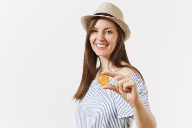 Młoda elegancka kobieta w niebieskiej sukience, kapeluszu z długimi włosami, trzymając monety bitcoin złotego koloru na białym tle. koncepcja online waluty wirtualnej życia ludzi. powierzchnia reklamowa. skopiuj miejsce