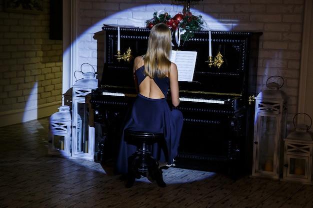 Młoda elegancka kobieta w sukni wieczorowej z odkrytymi plecami gra na pianinie w stylu retro wnętrza. ciemne kolory i widok z tyłu.