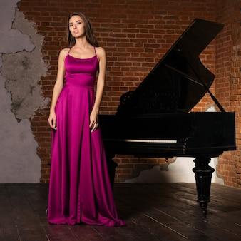 Młoda elegancka kobieta w wieczorowej sukni stojącej w pobliżu fortepianu we wnętrzu w stylu retro.