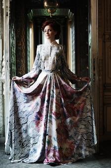 Młoda elegancka kobieta z latającą sukienką w pokoju pałacowym
