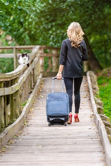 Młoda elegancka kobieta z torbą podróżną na drewnianej kładce w parku, widok z tyłu