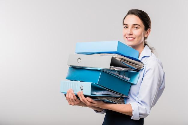 Młoda elegancka księgowa ze stosu folderów z dokumentami finansowymi, patrząc na ciebie