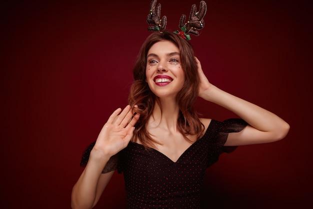 Młoda elegancka ładna brunetka kobieta ubrana w odświętną czarną sukienkę, patrząc radośnie na bok i szeroko uśmiechnięta, przygotowująca się do imprezy noworocznej