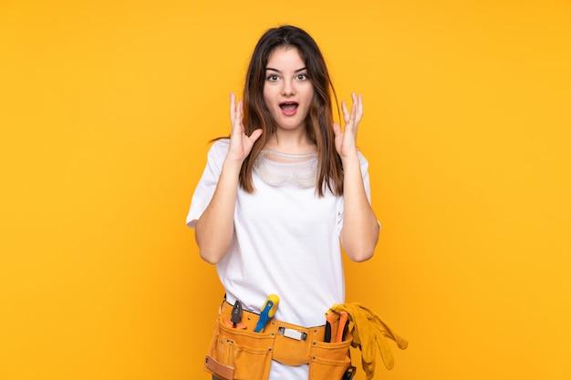 Młoda elektryk kobieta na kolor żółty ścianie z niespodzianka wyrazem twarzy