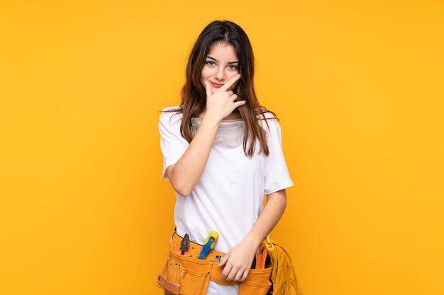 Młoda elektryk kobieta na żółtej ścianie myśląc pomysł