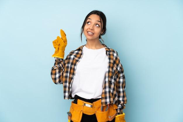 Młoda elektryk kobieta odizolowywająca na błękit ścianie z palcami krzyżuje i życzy najlepszy