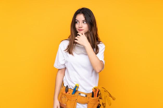Młoda elektryk kobieta odizolowywająca na żółtym główkowaniu pomysł