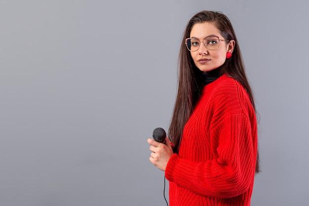 Młoda, emocjonalna brunetka z mikrofonem ubrana w czerwony sweter śpiewa na karaoke lub mówi przemówienie, odizolowane na szaro