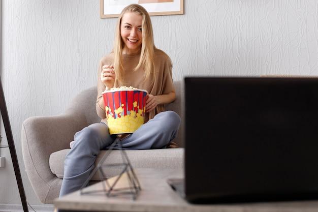 Młoda emocjonalna kobieta z popcornem na kanapie w domu