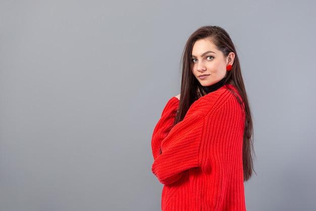 Młoda emocjonalna nastoletnia kobieta w okularach ubrana w czerwony sweter pozowanie na szarym tle