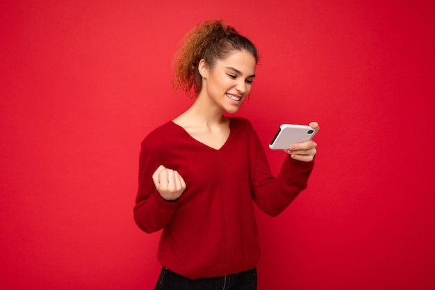 Młoda emocjonalna szczęśliwa kobieta ubrana w ciemnoczerwony sweter na białym tle na czerwonym tle, trzymając smartfon