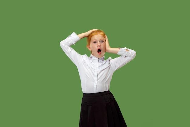 Młoda emocjonalna zaskoczona dziewczyna stoi z otwartymi ustami