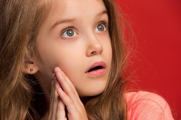 Młoda emocjonalna zaskoczona dziewczyna stojąca z otwartymi ustami