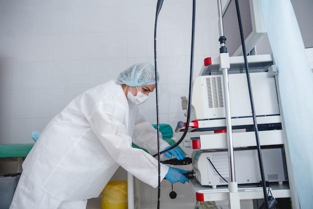 Młoda endoskopistka w białej czapce ochronnej i rękawiczkach przygotowuje sprzęt do pracy
