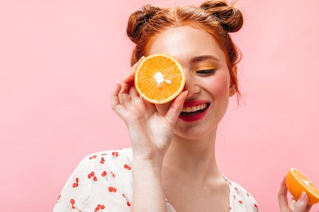 Młoda energiczna rudowłosa kobieta w białej koszulce trzyma smaczne pomarańcze na różowym tle.