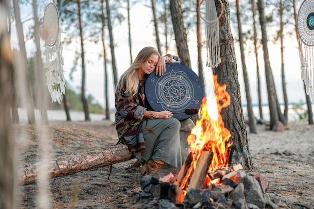 Młoda etniczna dojrzała szamanka chodzi i gra na bębnach medytacyjną muzykę