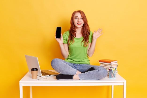 Młoda europejka pokazująca inteligentny telefon, siedząca na stole ze skrzyżowanymi nogami, ubrana w zieloną koszulkę i dżinsy, pokazująca telefon z pustym ekranem i podnosząca rękę, ma zaskoczony wyraz twarzy.