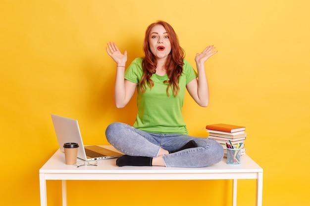 Młoda europejka pracująca w pomieszczeniach, przy komputerze przenośnym, z wyrazem zaskoczenia i podekscytowaną twarzą, odizolowana na żółtym tle, trzyma usta otwarte i rozkłada dłonie na bok.