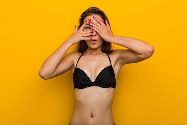 Młoda europejka w bikini mruga przez palce przestraszona i zdenerwowana.