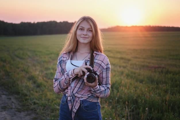 Młoda europejka z aparatem w letni wieczór o zachodzie słońca, robienie zdjęć