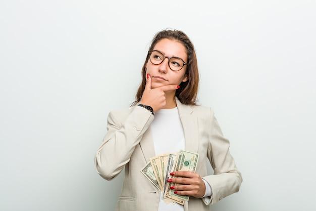 Młoda europejska biznesowa kobieta trzyma dolarowych banknoty patrzeje z ukosa z wątpliwym i sceptycznym wyrażeniem.