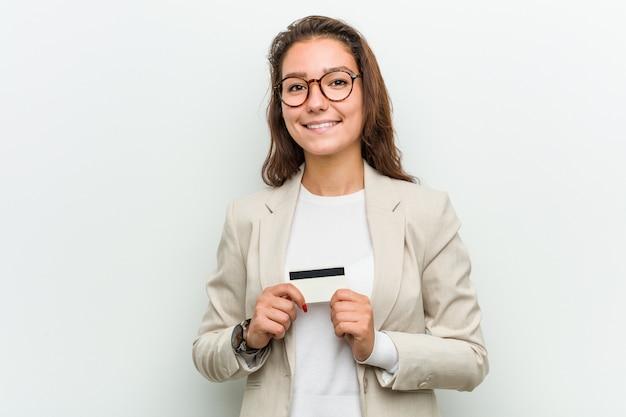 Młoda europejska biznesowa kobieta trzyma kartę kredytową szczęśliwą, uśmiechniętą i rozochoconą.
