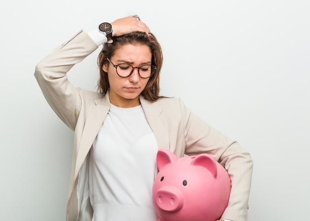 Młoda europejska biznesowa kobieta trzyma skarbonkę, będąc w szoku, przypomniała sobie ważne spotkanie.