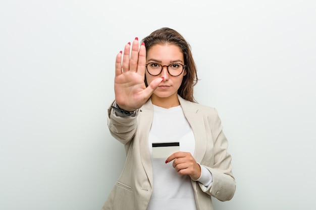 Młoda europejska bizneswoman trzyma kartę kredytową stojącą z wyciągniętą ręką pokazując znak stopu, uniemożliwiając ci.