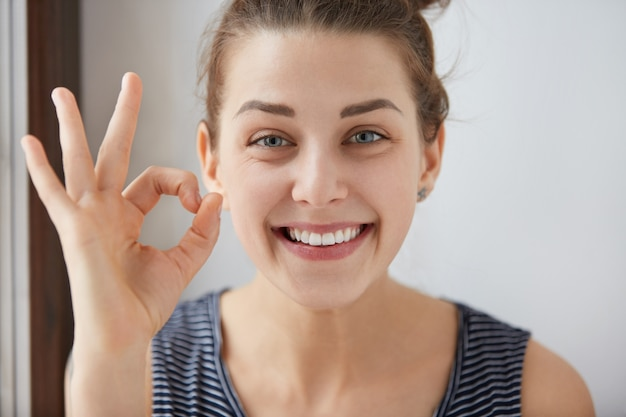 Młoda europejska brunetki kobieta pokazuje gest palcami. szczęśliwa kobieta w pasiastej górze, uśmiechając się o niebieskich oczach. jej białe zęby i radosna buźka dowodzą, że wszystko idzie zgodnie z planem.