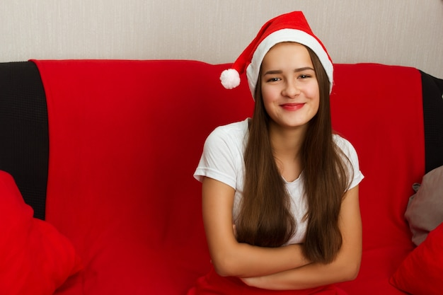 Młoda europejska dziewczyna z długimi ciemnymi włosami w czapce świętego mikołaja siedzi na kanapie i uśmiecha się