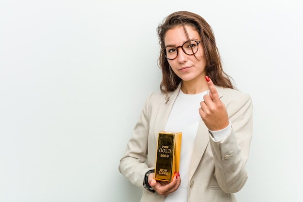 Młoda europejska kobieta biznesu trzyma sztabkę złota, wskazując palcem na ciebie, jakby zapraszając podejść bliżej.