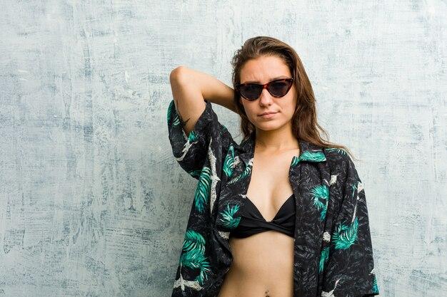 Młoda europejska kobieta jest ubranym bikini cierpienia szyi ból z powodu siedzącego stylu życia.
