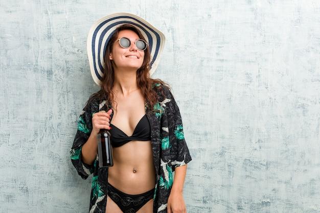 Młoda europejska kobieta jest ubranym bikini i pije piwo
