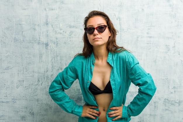 Młoda europejska kobieta jest ubranym bikini łaja kogoś bardzo gniewnego.