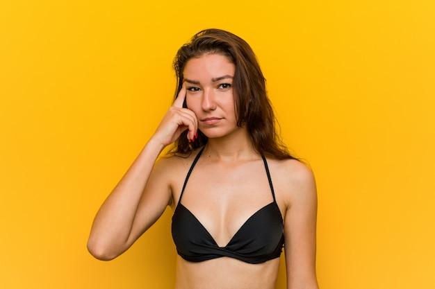 Młoda europejska kobieta jest ubranym bikini pokazuje rozczarowanie gest z palcem wskazującym