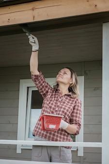 Młoda europejska kobieta maluje werandę nowego drewnianego domu