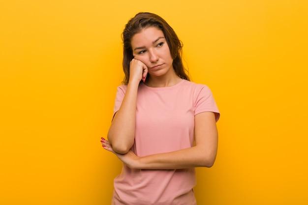 Młoda europejska kobieta na białym tle nad żółtym, która czuje się smutna i zamyślona, patrząc na miejsce.
