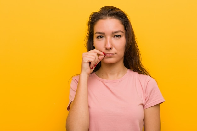 Młoda europejska kobieta odizolowywająca nad kolor żółty ścianą z palcami na wargach utrzymuje sekret.