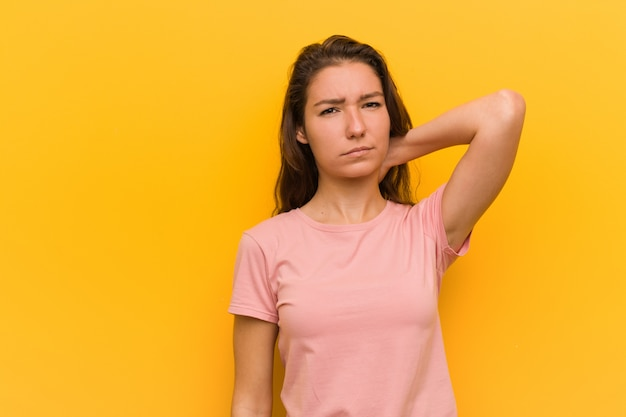 Młoda europejska kobieta odizolowywająca nad kolor żółty ściany cierpienia bólem szyi z powodu siedzącego trybu życia.