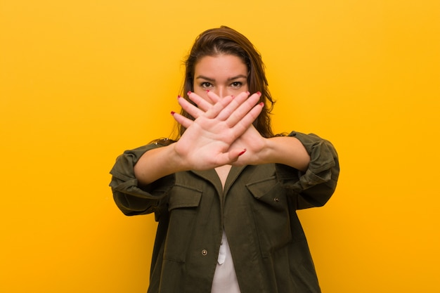 Młoda europejska kobieta odizolowywająca nad kolorem żółtym robi zaprzeczenie gestowi