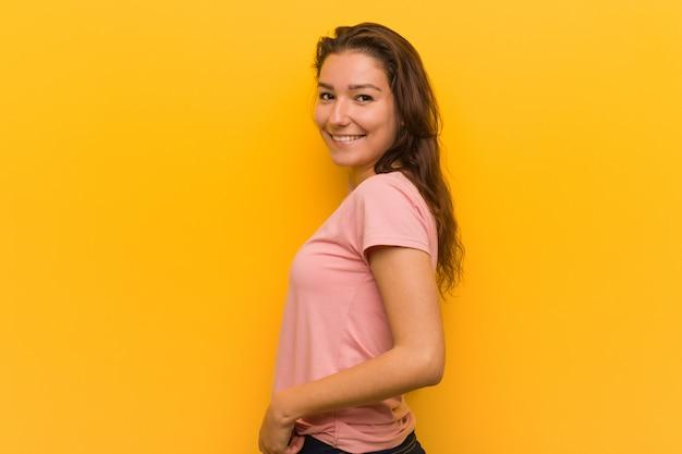Młoda europejska kobieta odizolowywająca nad żółtymi spojrzeniami na boku ono uśmiecha się, wesoło i przyjemny.