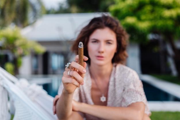Młoda europejska kobieta pali cygaro, leżąc na hamaku przed tropikalnym luksusowym hotelem willa, naturalne światło słońca