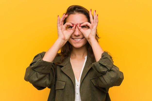 Młoda europejska kobieta pokazuje ok podpisuje jej oczy