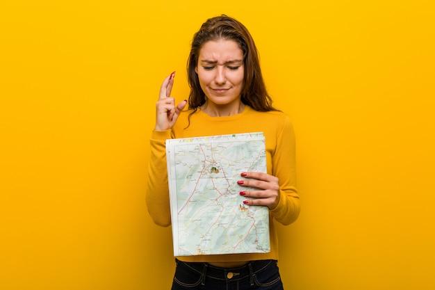 Młoda europejska kobieta trzyma mapę krzyżuje palce dla mieć szczęście