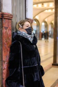 Młoda europejska kobieta w ochronnej jednorazowej czarnej masce medycznej w metrze. ochrona koncepcji niebezpiecznego koronawirusa grypy 2019-ncov, zmutowanego i rozprzestrzeniającego się w chinach