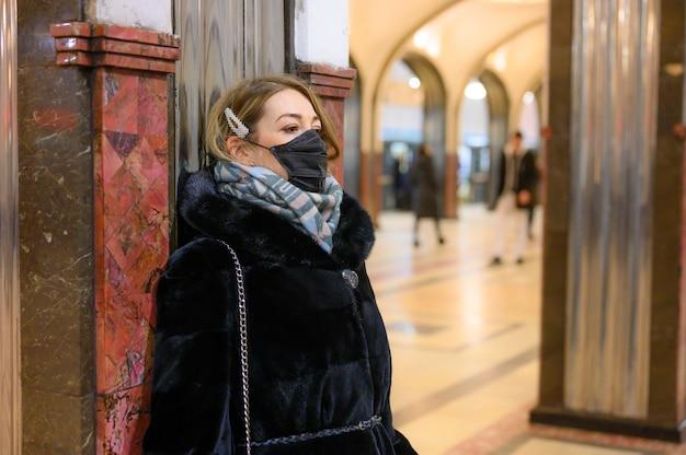 Młoda europejska kobieta w ochronnej jednorazowej czarnej masce medycznej w metrze.