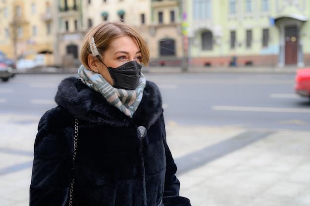 Młoda europejska kobieta w ochronnej jednorazowej czarnej masce medycznej w mieście na świeżym powietrzu. ochrona koncepcji niebezpiecznego koronawirusa grypy 2019-ncov, zmutowanego i rozprzestrzeniającego się w chinach