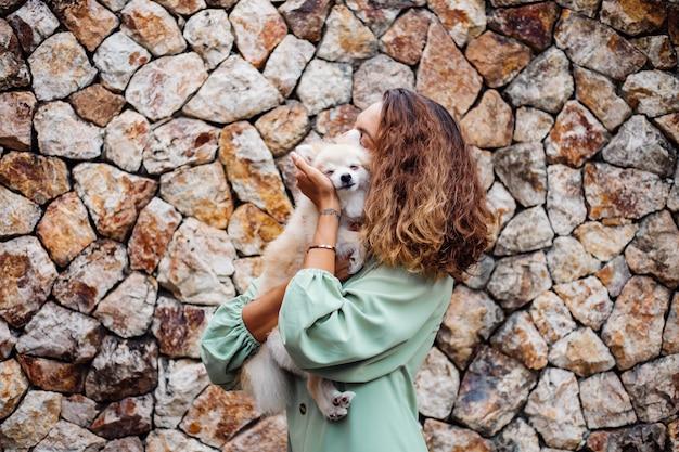 Młoda europejska kobieta w romantycznej letniej sukience bransoletka trzyma ślicznego puszystego pomorskiego szczeniaka szpic na zewnątrz willi
